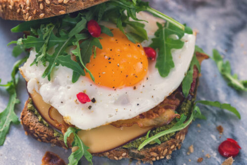 Slice of rustic homemade bread with ham,fried eggs,arugula and cheese for the breakfast